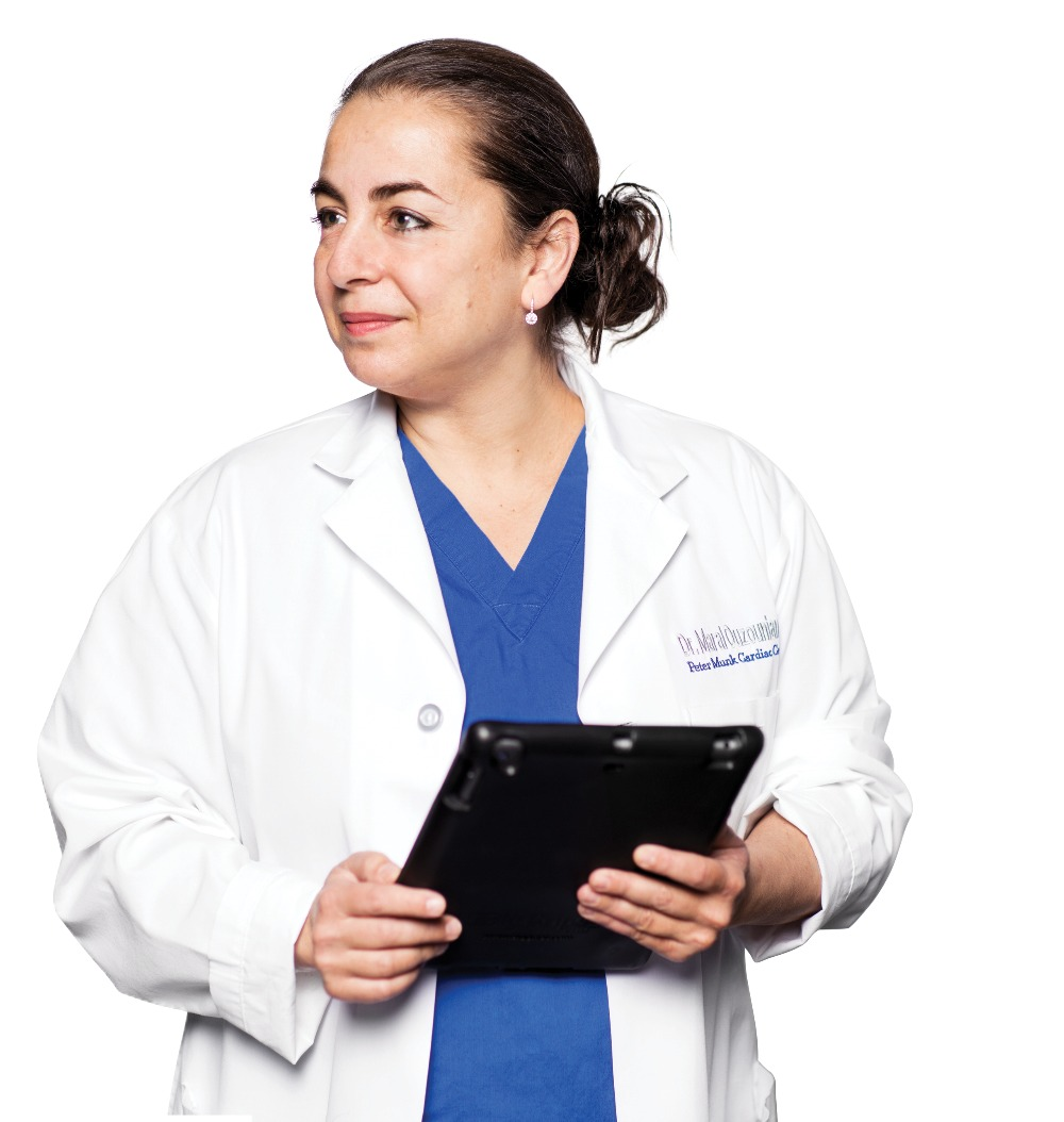 Dr. Maral Ouzounian wearing a lab coat and holding a lab coat, she is looking to her right, smiling slightly